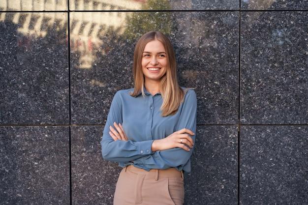 Colpo di bella giovane donna di affari che indossa la camicia di chiffon blu mentre levandosi in piedi con le braccia conserte sul muro di marmo grigio