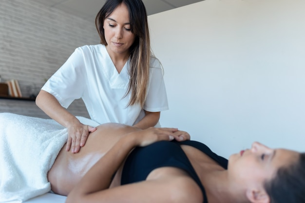 Shot of beautiful young physiotherapist woman massaging tummy on pregnant woman on a stretcher at home.