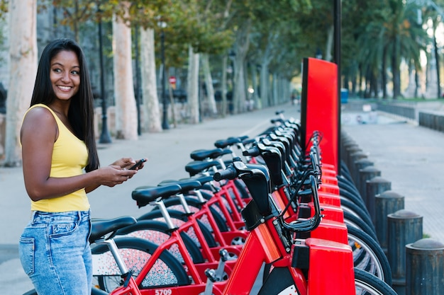 Shot of beautiful young woman checking her mobile phone while renting a bike in a city