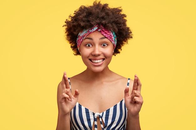 Colpo di donna nera con espressione allegra, incrocia le dita, desidera essere fortunato per azioni future