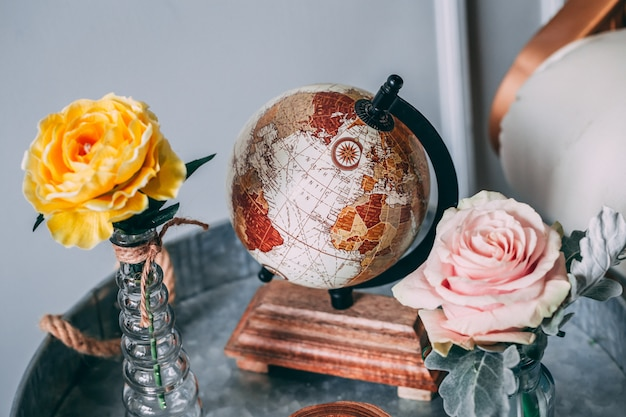 Shot of a brown world globe beside yellow and pink roses in vases