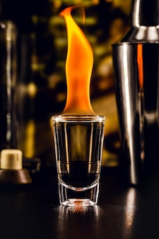 Shot of burning hot tequila drink, shot of alcoholic drink with fire, bar setting