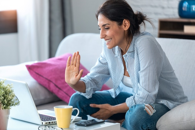 Shot of business woman waving while having an online video call via laptop computer and working remotely from home.