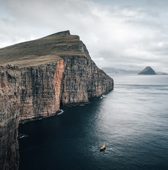 Shot capturing the beautiful nature of the faroe islands, a boat floating in the sea by the cliffs