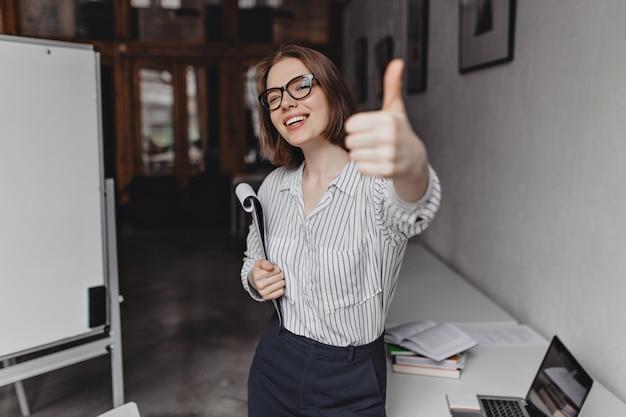 Colpo di affascinante donna d'affari con gli occhiali che mostra i pollici in su e posa con un'enorme quantità di documenti in ufficio.