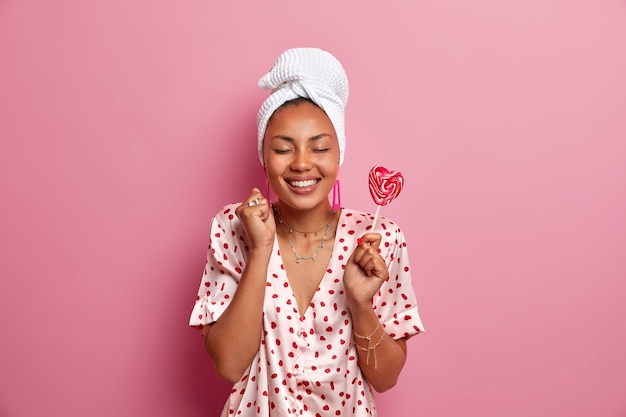 Shot of cheerful dark skinned female model has healthy complexion, broad smile, white teeth, stands with eyes closed, clenches fist, wears wrapped towel on head, pajama, holds lollipop in hand