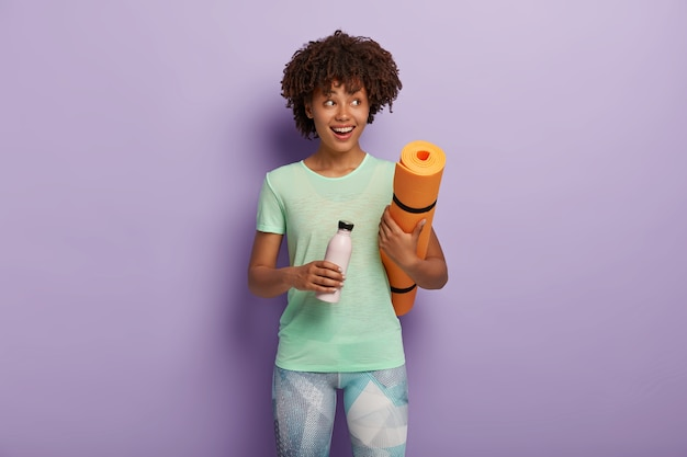 Shot of cheerful dark skinned girl holds fitness mat and bottle of fresh water, drinks during exhausted exercising looks right dressed in active wear poses indoor. motivation, healthy lifestyle