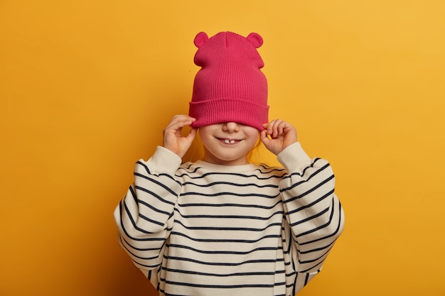 Shot of cheerful girl has two stick out teeth, covers half face with hat, wears casual striped jumper, has fun, gets dressed and prepares for outdoor walk, isolated on yellow wall