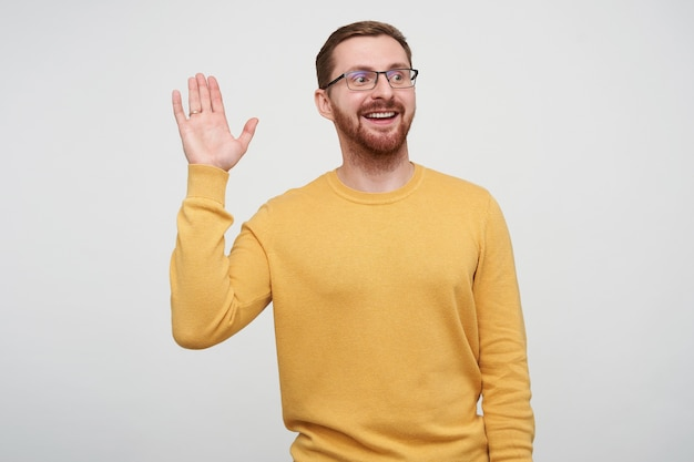 Shot of cheerful young handsome brown haired bearded guy in eyewear raising palm in hello gesture while looking positively aside with sincere smile, posing in mustard pullover