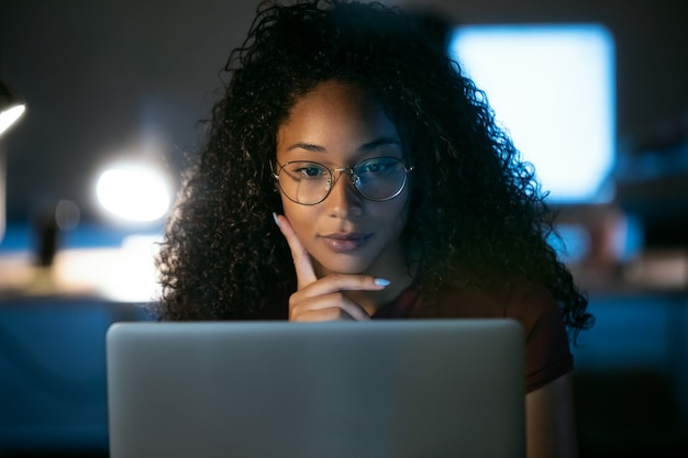Shot of confident young business woman working with laptop sitting in the office.