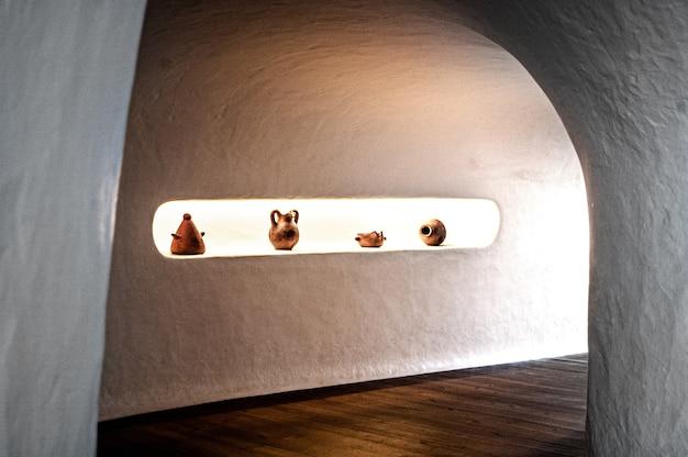 Inquadratura di un corridoio con pareti bianche e pavimento in legno con alcuni vasi di ceramica ea lanzarote, spagna
