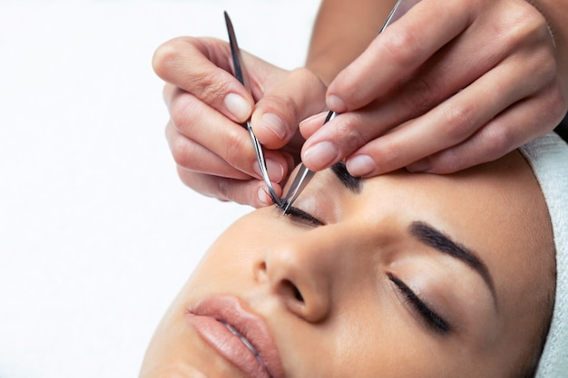 Shot of cosmetologist doing the eyelash extension procedure on a woman over white background.