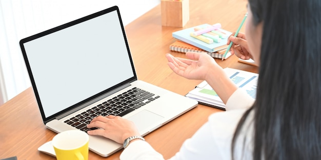 Behind shot of creative woman working on computer laptop with white blank screen that putting on wooden working desk and surrounded by office equipment and stationary as background.