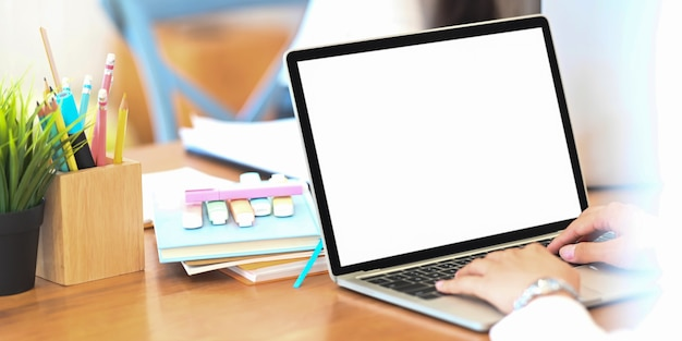 Behind shot of creative woman working on computer laptop with white blank screen that putting on wooden working desk.
