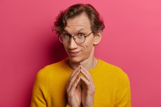 Shot of curious young caucasian man steepls fingers, looks with intention to do something, wears round spectacles and yellow jumper, has some plans in mind, isolated over pink wall