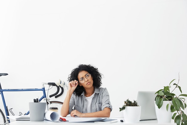 Shot of cute young entrepreneur with dark curly hair wearing shirt and round eyeglasses