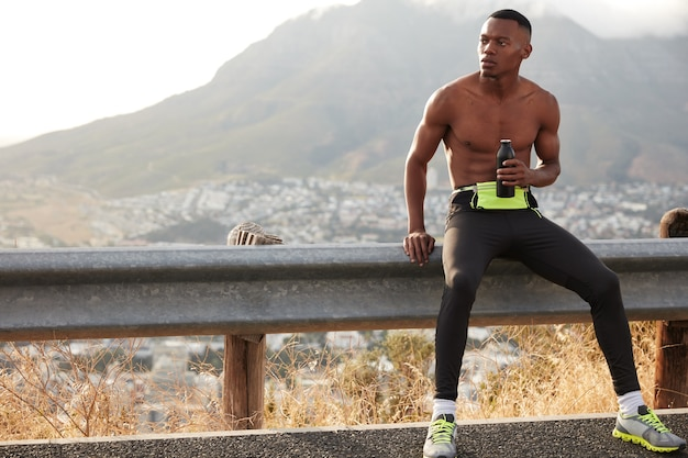 Shot of dark skinned man has intensive preparation to sport competitions, holds bottle of water, looks thoughtfully aside, wears sneakers and leggings, full of energy.