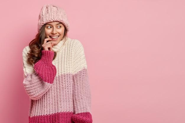 Colpo di donna positiva felice guarda da parte con un sorriso piacevole, essere di buon umore, si sente gioia, vestito con abiti invernali alla moda, modelli contro il muro rosa, copia spazio sulla destra