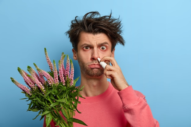 Shot of displeased man suffers from seasonal allergy, drips nose with nasal spray, holds plant causing sneezing, tired of constant treatment, tries to find good quality remedy. seasonal health issues