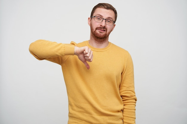 Inquadratura di un giovane maschio barbuto dispiaciuto con i capelli corti castani, torcendo la bocca con il broncio e indicando con il pollice verso il basso, indossando un maglione senape mentre è in piedi