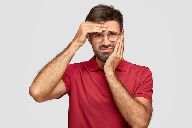 Shot of dissatisfied bearded male has toothache and headache, feels unhappy and tired after long work, frowns face in discontent, dressed in red t-shirt, isolated over wall