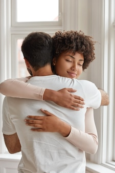 Shot of diverse couple cuddle each other