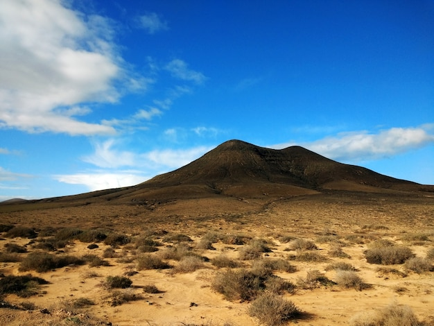 Shot of a dry wasteland and a mountain in the distance in corralejo natural park, spain