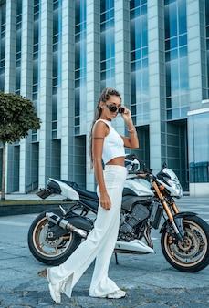 Shot of elegant woman posing against motorbike and building