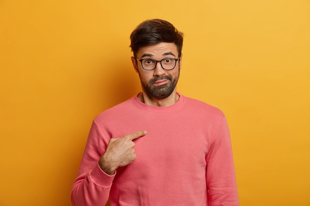 Shot of emotional bearded man points at himself, surprised being chosen, asks question with shocked hesitant expression, wears rosy sweater, eyewear, poses against yellow wall. who, me?