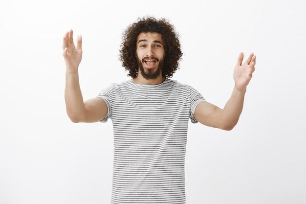 Inquadratura di un fratello ispanico di bell'aspetto emotivo con barba e capelli ricci, che alza i palmi e urla, vede una persona familiare e attira l'attenzione