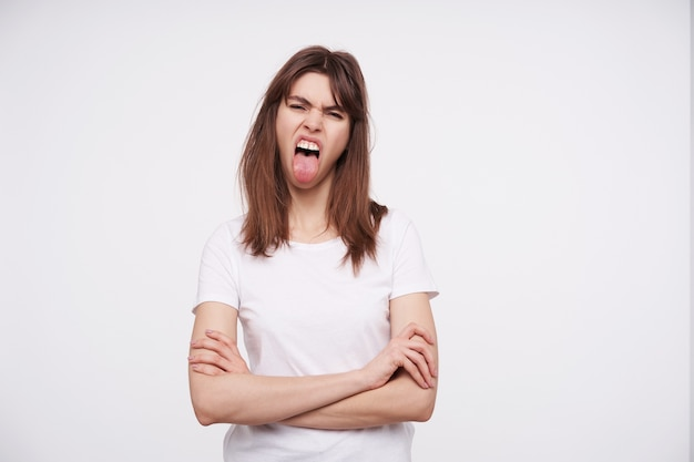 Shot of excited young brunette female with casual hairstyle crossing hands on her chest and sticking out her tongue while posing over white wall in basic t-shirt