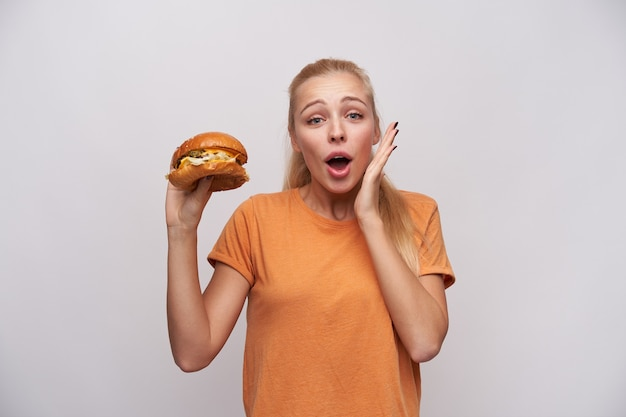 Shot of excited young lovely blonde woman with casual hairstyle looking at camera with opened mouth and raising palm emotionally, can't wait to eat her tasty bugrer, isolated over white background