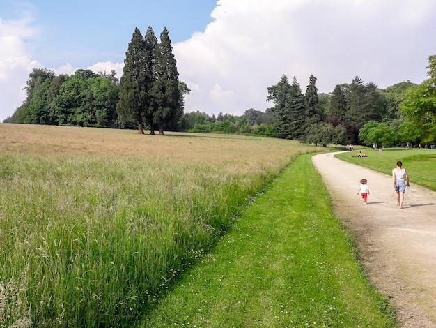 Inquadratura di una donna con un bambino che cammina su un sentiero nel parco in una giornata di sole