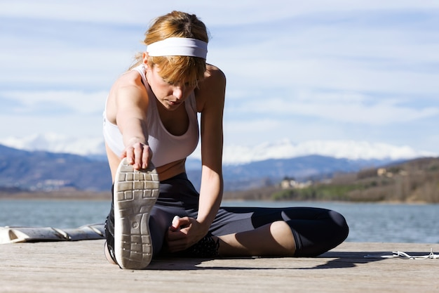 Shot of fit and sporty young woman doing stretching next to the lake.