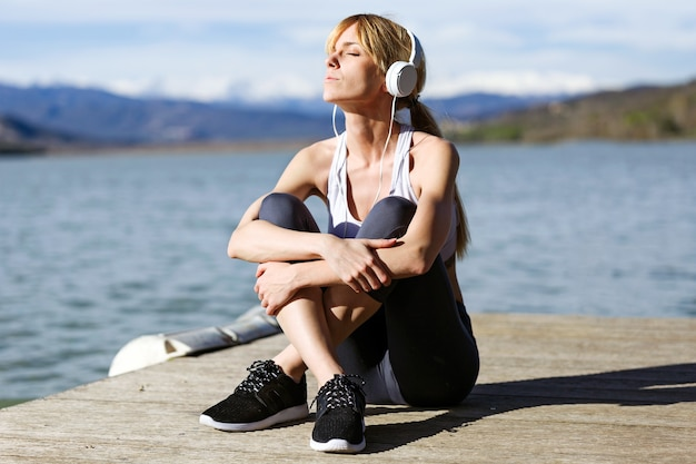 Shot of fit and sporty young woman relaxing and listening to music after work out next to the lake.