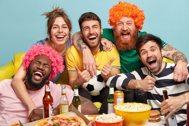 Shot of friendly companions embrace and smile happily, cheer with winning favorite team, have nice time together watching exciting football game, drink beer and eat fast food. funny fans support