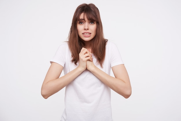 Shot of frightened young brunette woman dressed in white basic t-shirt keeping her raised hands together and showing her teeth while looking  with puzzled face, isolated over white wall