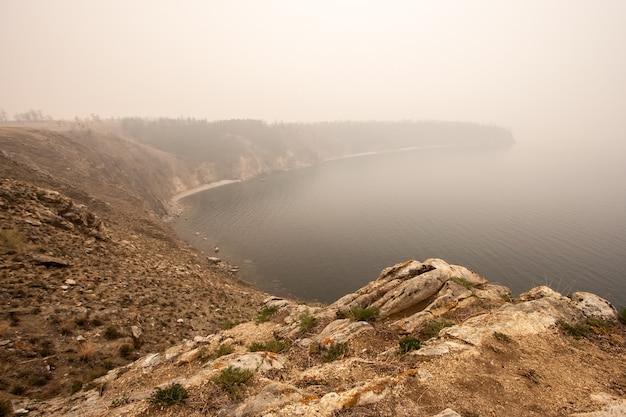霧の中で高い崖のバイカル湖から撮影