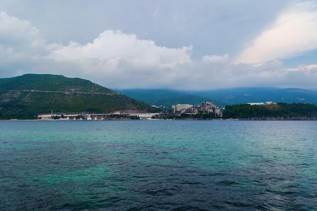 밝고 화창한 날 바다의 요트 클로즈업과 해안의 아름다운 산 풍경에서 촬영