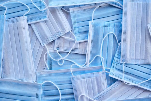 파란색과 흰색 양쪽에 무작위로 배치된 새로운 수술용 마스크 더미 위에서 샷
