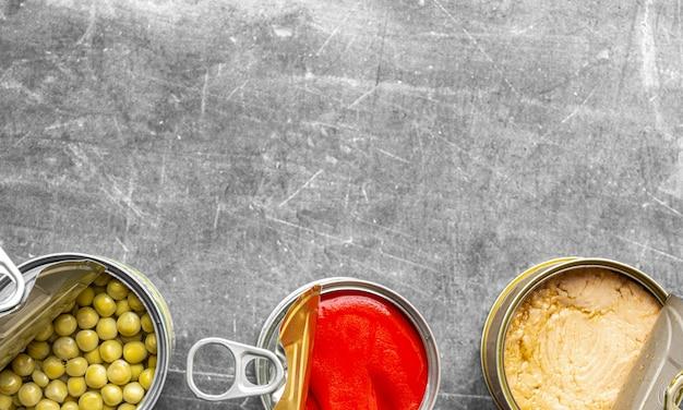 赤唐辛子、明るいマグロ、エンドウ豆の灰色の表面と柔らかな自然光の開いた画像の下部に並んでいる缶詰の3つの缶の上から撮影