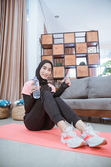 Съемка снизу: мусульманка в спортивном костюме хиджаб сидит на полу и держит бутылку с питьевой водой в гостиной