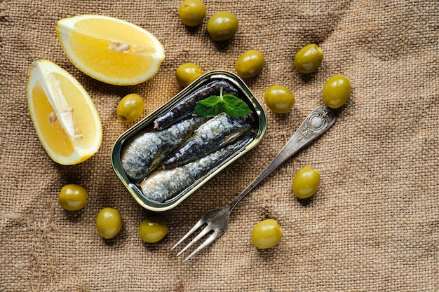 Shot from above of a can of sardines in oil, with some basil leaves, lemon wedges and olives on sackcloth