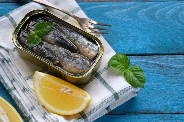 Shot from above of a can of sardines in oil, with some basil leaves and a piece of lemon on a blue rustic table