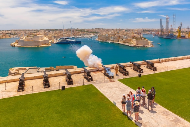 Shot from cannon at noon in saluting battery at fort lascaris as seen from upper barrakka gardens, with grand harbor, senglea and brigu on the background, valletta, malta.