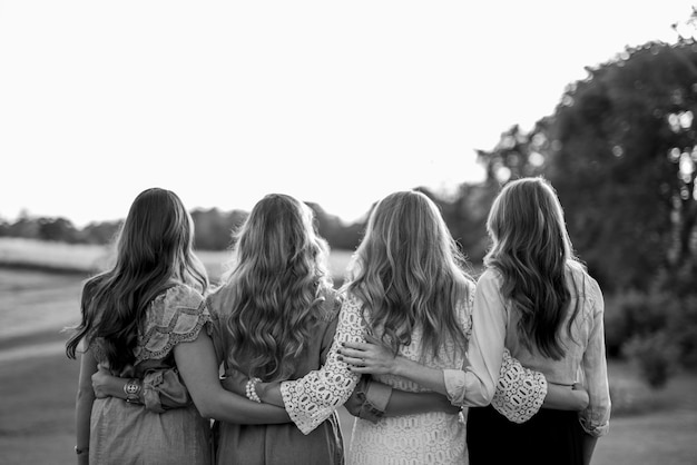 Shot from behind of four female with their arms around each other in black and white