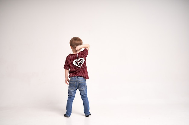 Shot from behind of little cute boy holding wooden heart with sign love on minimalistic white backgr...