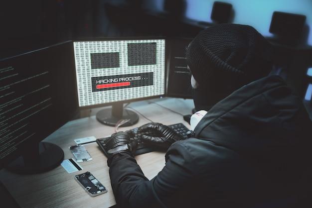 Снимок со спины: хакер в капюшоне взламывает корпоративные серверы данных из своего подземного убежища. в месте темная атмосфера, несколько дисплеев
