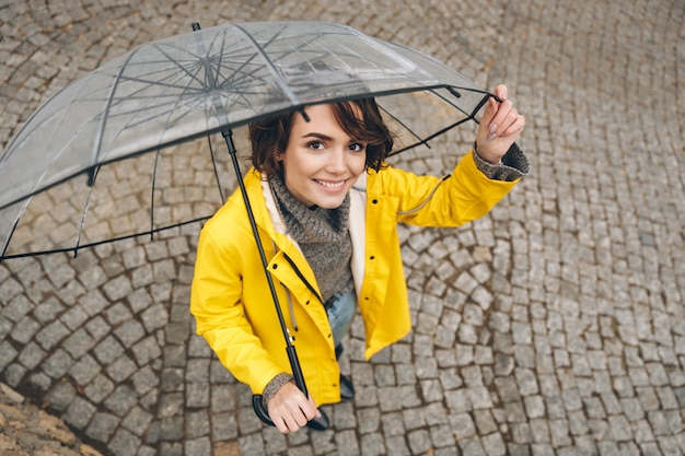 Shot from above of wonderful woman in yellow raincoat being happy while walking under big transparent umbrella