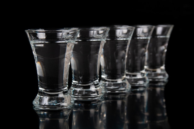 Shot glass with tequila and vodka on a black table